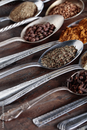 Foto op Aluminium Aromatische Different spices in spoons on a wooden background.