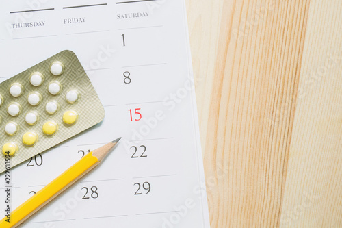 Close up Contraceptive control pills on date of calendar
