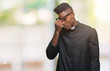Young african american priest man over isolated background tired rubbing nose and eyes feeling fatigue and headache. Stress and frustration concept.