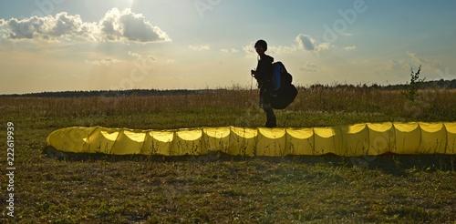 девушка с парапланом на поле перед взлетом