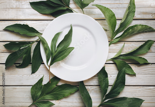 Top view empty white plate on light gray rustic wooden background with green leaves of peony.