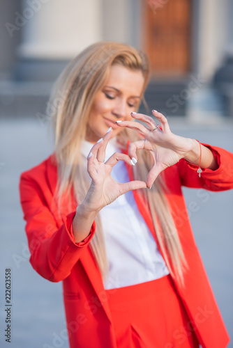 Fotografia  Beautiful blonde in a red jacket and pants on a building background with columns