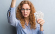 Young redhead woman over grey grunge wall holding dollars annoyed and frustrated shouting with anger, crazy and yelling with raised hand, anger concept