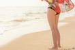 Schlanke Frau in Bademode steht am Sandstrand