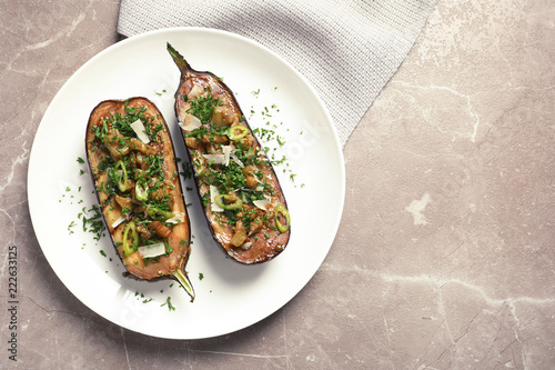 Flat lay composition with plate of stuffed eggplants and space for text on gray table