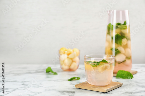 Glass with tasty melon ball drink on table. Space for text