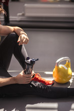 Male Athlete Preparing For Workout With Kettlebells In Gym. Male Athlete Getting Ready For Training. Sportboots And Active Lifestyle Concept. Close-up