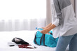Young woman packing sports stuff for training into bag in bedroom. Space for text