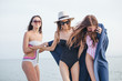 group of smiling young women on beach with plaid after evening , summer vacation, holidays, travel and people concept