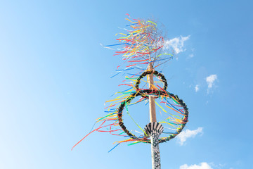 typical greman may pole or maibaum at the festival in front of blue sky, spring holiday concept