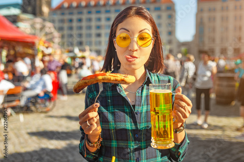 Young happy asian traveler woman eating fried sausage and drinks mug of beer at the fair market square in Germany, beer and food festival concept