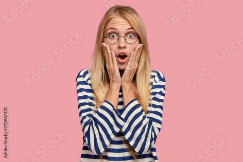 Photo of amazed blonde model keeps palms on cheeks, reacts on unexpected news from friend, stares through round transparent glasses, isolated over pink background Canvas Print