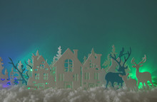 Magical Christmas Paper Cut Winter Background Landscape With Houses, Trees, Deer And Snow In Front Of Northern Lights Background.