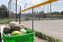 Bucket With Baseballs And Softballs With Field As Background In Daylight