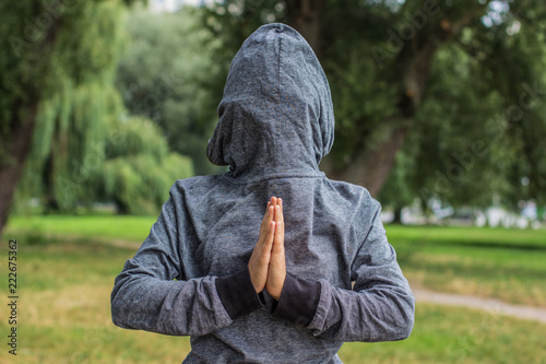 Fotografie, Tablou  creative prayer pose by human hands concept shot with backwards clothes gray hoo