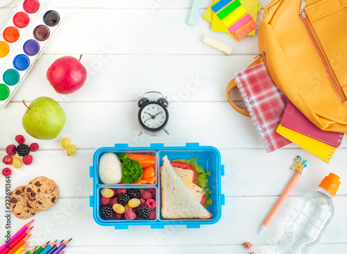 Open lunch box near clock, school accessories and backpack