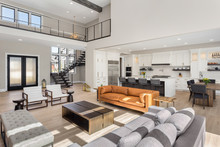 Beautiful Living Room Interior In New Luxury Home With Open Concept Floor Plan. Shows Entry, Stairs, Kitchen, And Dining Room.