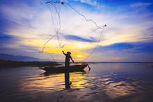 Silhouette Fisherman Throwing Fishing Net During Sunrise