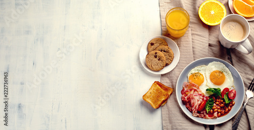 Breakfast with fried eggs, bacon, orange juice, yogurt and toasts