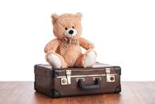 Old Teddybear Sitting On Vintage Suitcase
