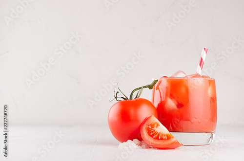 Foto op Canvas Cocktail Tomato alcohol beverage in glass with ice cubes, tomato, straw, salt and juicy slice on white wood table, copy space.