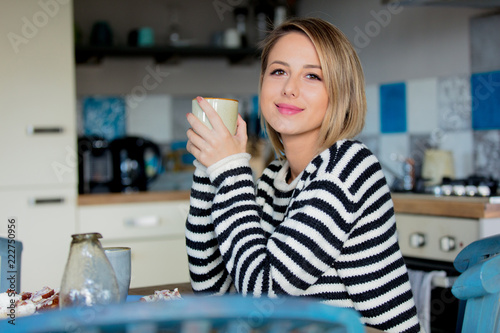 Obraz Young lady in sweater sitting at the table in breakfast time with cup of coffee and cake at the kitchen. - fototapety do salonu