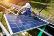 Leinwanddruck Bild Professional worker installing solar panels on the green metal construction, using different equipment, wearing helmet. Innovative solution for energy solving. Use renewable resources. Green energy.