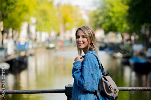 Young girl in jeans jacket and backpack at bridge in Amsterdam street. Holland, Netherlands