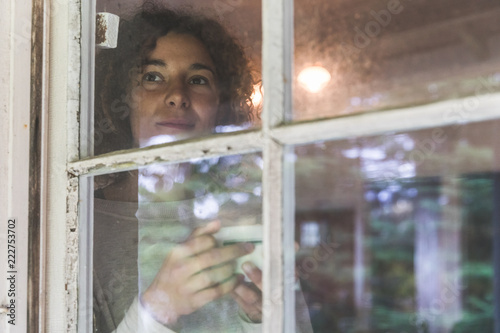Woman drinking coffee and looking out through an old window Fototapet