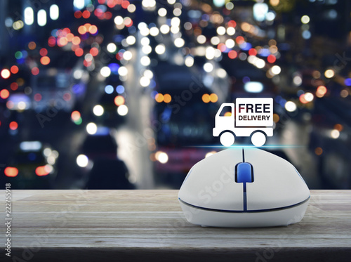 Free delivery truck flat icon with wireless computer mouse on wooden table over blur colorful night light city with cars in city, Business free delivery online concept