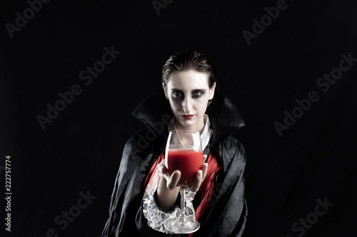 Fototapeta Woman dressed up as a vampire for halloween holding glass of red drink