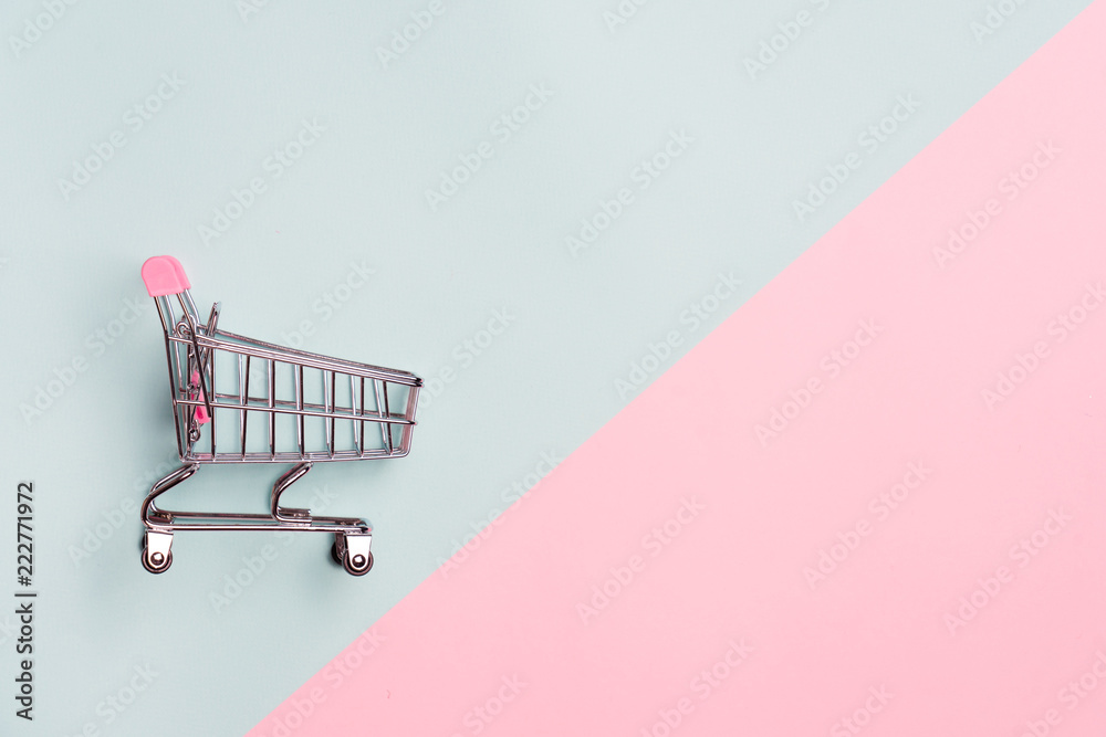 Fototapeta Close up of supermarket grocery push cart for shopping with black wheels on white background. Concept of shopping.