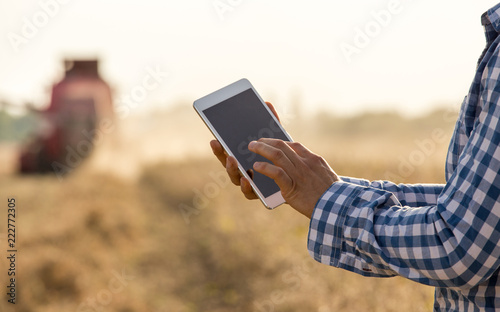 Photo Farmer working on tablet in field during hrvest