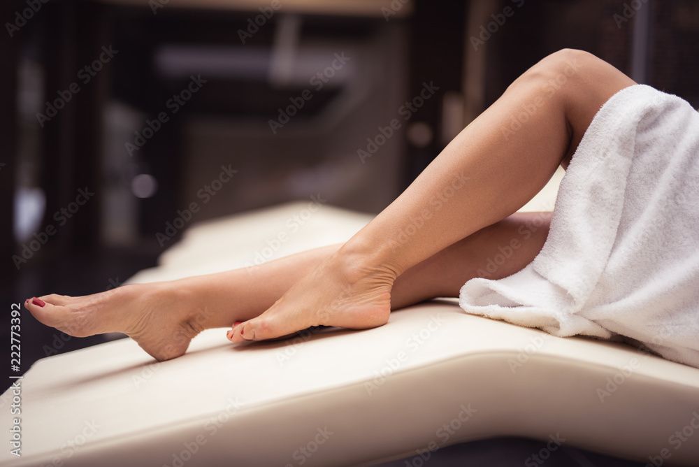 Fototapeta My lower body. Close up of female legs with perfect skin. Woman relaxing on daybed at spa lounge
