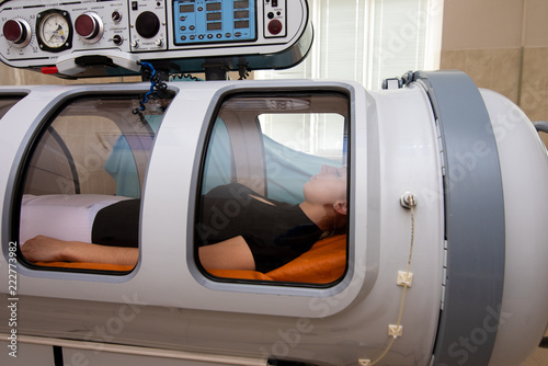 beautiful girl in a black T-shirt and white pants lies in a hyperbaric chamber Canvas-taulu