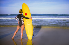 Back View Of Young Attractive And Sporty Surfer Girl In Cool Swimsuit At The Beach Holding Yellow Surf Board Looking At The Blue Sea N In Summer Surfing Holidays