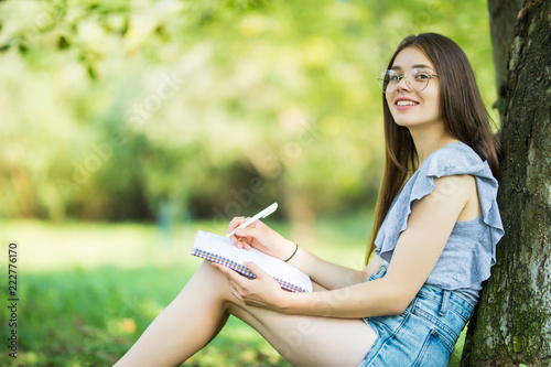 Side view of concentrated brunette woman in eyeglasses sitting near the tree in Canvas-taulu