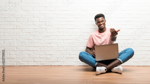 Photo  Afro american man sitting on the floor with his laptop presenting and inviting t