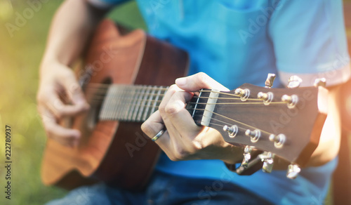 Fotografie, Obraz  The man is playing guitar in the garden, Close-up male hand playing on acoustic guitar outdoor with bokeh and rays of sunlight