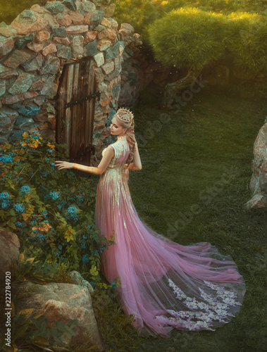 Photo cute princess wearing long pink dress with trailer and is walking in the garden and touching flowers in soft sun lights