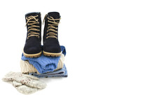 A Pile Of Clothes With Boots Are On A White Background