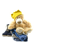 Soft Toy Sits On A Pale Of Clothes On A White Background