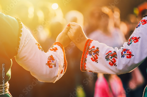 Fényképezés Girls in traditional Bulgarian ethnic costumes with red dresses and patterns on white shirts holding hands in the sunset