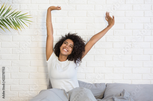 Beautiful black woman waking up in her bed Canvas Print