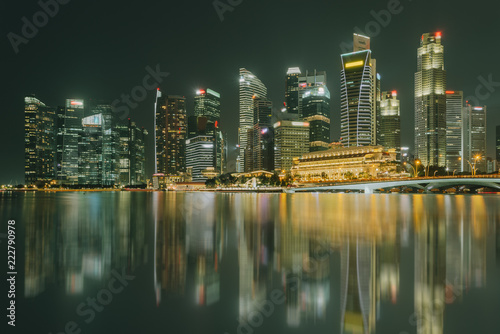 Tuinposter Singapore Singapore city skyline. Business district view. Downtown reflected in water at night in Marina Bay. Travel cityscape