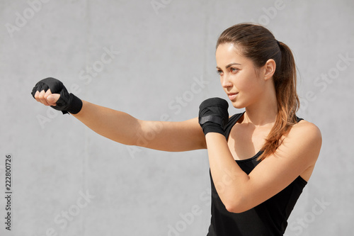 Sideways shot of attractive sporty woman boxer has bandages on hands, practices boxing, ready to defense herself, gestures aside, isolated over gray concrete wall. female fighter stands indoor