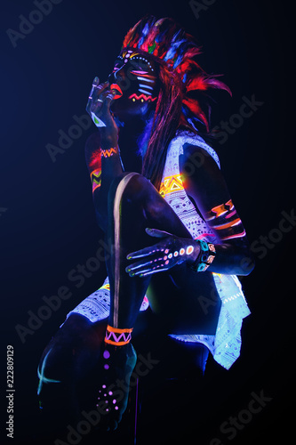 Woman with a neon makeup in ultraviolet light - 222809129