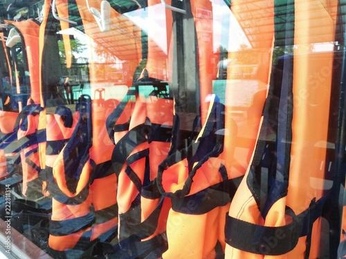 Foto op Aluminium Graffiti An orange life jacket hanging in a glass cabinet.
