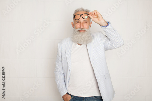 Cheerful happy mature man in glasses looking camera and smiling over white wall