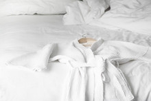 White Bath Robe On The Bed In ...